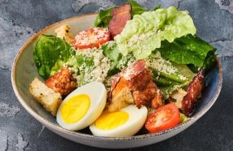 Склад: айсберг, ромен, курка бедро, соус Цезар, крутони, бекон, пармезан, коктейльний томат, яйце куряче.